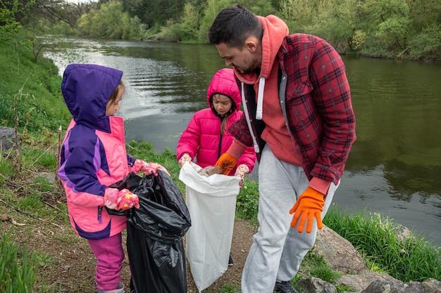 Kinderen en papa ruimen afval op in het bos bij de rivier.