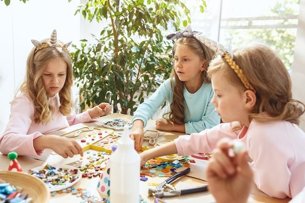 Kinderen en verjaardagsdecoratie. jongens en meisjes aan tafel met eten, gebak, drankjes en feestgadgets.