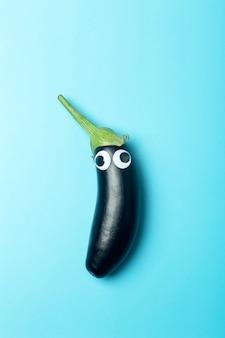 Kinderen eten concept. aubergine met ogen op een gekleurde blauwe achtergrond. grappige groenten en eten voor kinderen