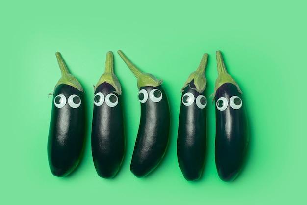 Kinderen eten concept. aubergine met ogen op een gekleurde groene achtergrond. grappige groenten en eten voor kinderen