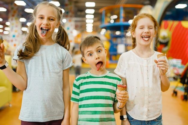 Kinderen eten ijs in het uitgaanscentrum. jongen en meisjes vrije tijd op vakantie, geluk uit de kindertijd, gelukkige kinderen op speelplaats