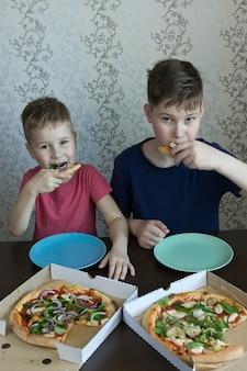 Kinderen eten pizza en pasta in café. kinderen die binnenshuis ongezond eten.