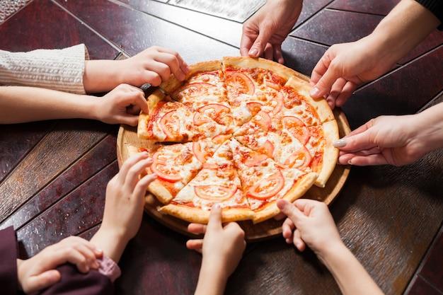 Kinderen eten pizza in een restaurant.