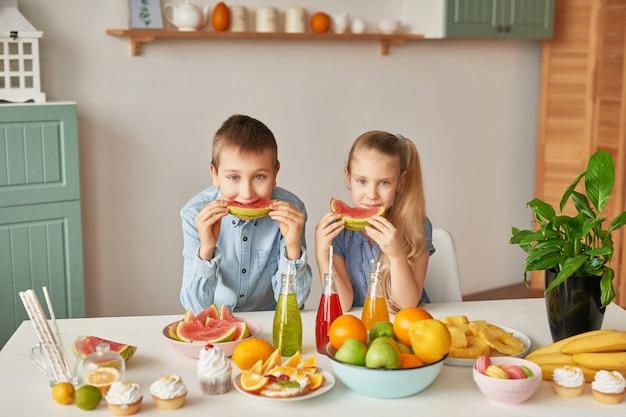 Kinderen eten watermeloenplakken in de keuken