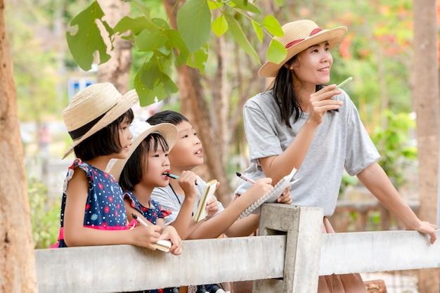 Kinderen familie reizen voor het leren van kennis buiten in de natuur