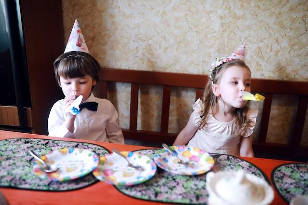 Kinderen feest in caps verjaardag vieren met taart en ballonnen thuis.