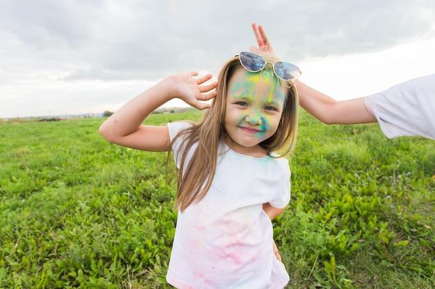 Kinderen, festival van holi en vakantieconcept - gelukkig klein meisje dat een zonnebril draagt bedekt met