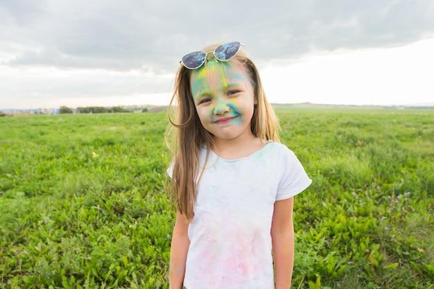 Kinderen, festival van holi en vakantieconcept - gelukkig meisje die zonnebril dragen die met kleurenpoeder over aardmuur glimlacht.
