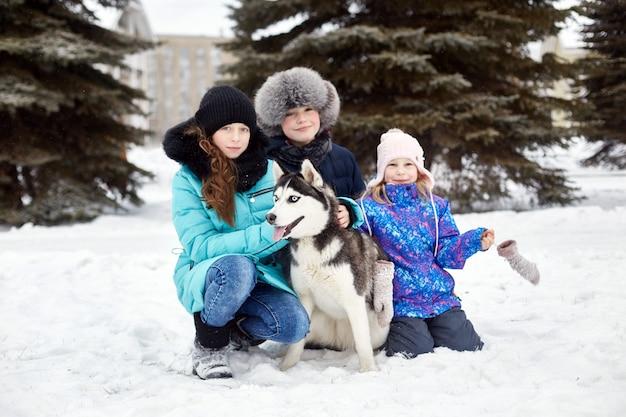 Kinderen gaan in de winter uit met husky's