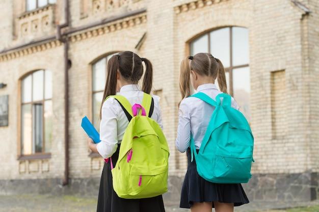 Kinderen gaan naar school schoolmeisjes met rugzakken, september concept.