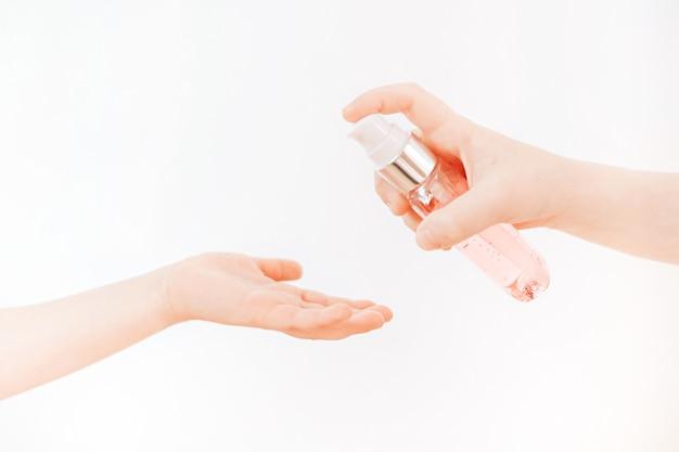 Kinderen gebruiken alcoholgel om handen te wassen om coronavirus covid-19 te voorkomen. voorkom het virus en de bacteriën