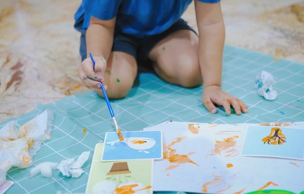 Kinderen gebruiken penselen om waterverf op papier te schilderen om hun verbeeldingskracht te creëren en hun leervaardigheden te verbeteren.