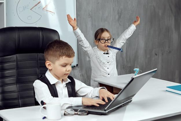 Kinderen gekleed in de afbeeldingen van kantoorpersoneel genieten van de vakantie. een kleine zakenvrouw feliciteert een collega met de vakantie. het concept van een vakantie op het werk. kinderen zijn de bazen.