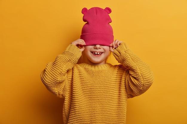 Kinderen, geluk, welzijn concept. zorgeloos speels meisje bedekt de helft van het gezicht met een hoed, probeert zich te verbergen voor iemand, draagt een losse gebreide trui, geïsoleerd op een gele muur, heeft een mooie glimlach