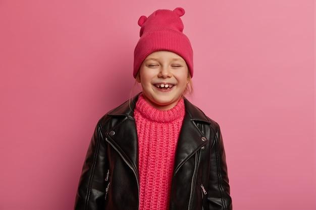 Kinderen, gelukkige emoties en oprechte gevoelens concept. dolblij klein schattig meisje lacht uit, dwazen rond met ouders, draagt hoed, gebreide trui en schuimjasje, drukt vreugde en geluk uit