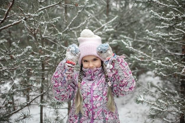 Kinderen genieten van de eerste sneeuw in het winterbos, actieve seizoensactiviteiten, levensstijl