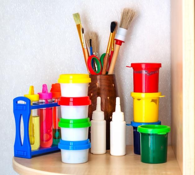 Kinderen gereedschap van de kunstenaar: verf, penselen op plank