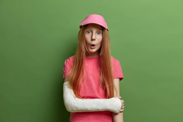 Kinderen, gezichtsuitdrukkingen concept. verrast sproeterig meisje kijkt met verwondering, heeft arm gebroken in het gips, draagt roze pet en t-shirt, geïsoleerd op groene muur, viel van fiets