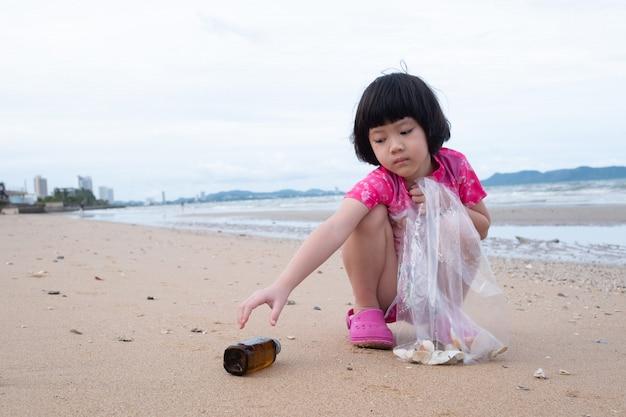 Kinderen halen afval op het strand, vuile zee