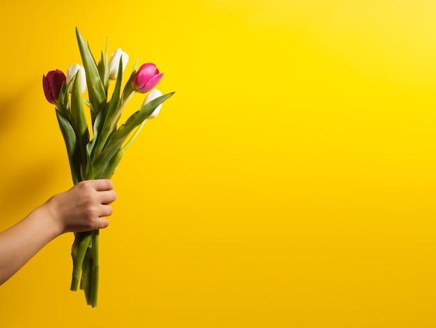 Kinderen hand met bloemen op gele achtergrond. boeket van witte en roze tulpen voor verjaardag, gelukkige moeders of valentijnsdag en 8 maart. stock foto