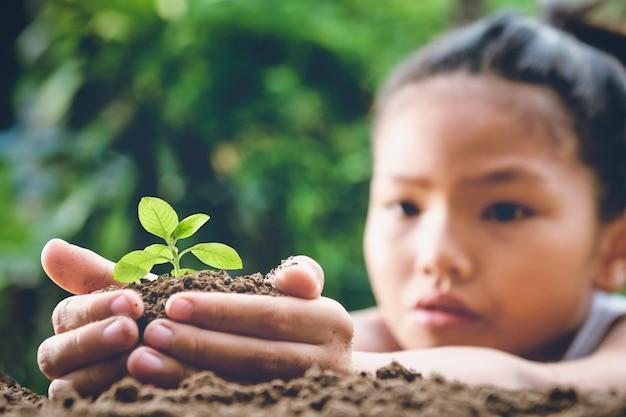 Kinderen hand met kleine boom voor planten in de tuin. concept groene wereld
