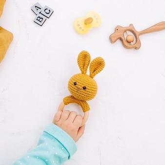 Kinderen hand met konijn zitzak op licht marmer