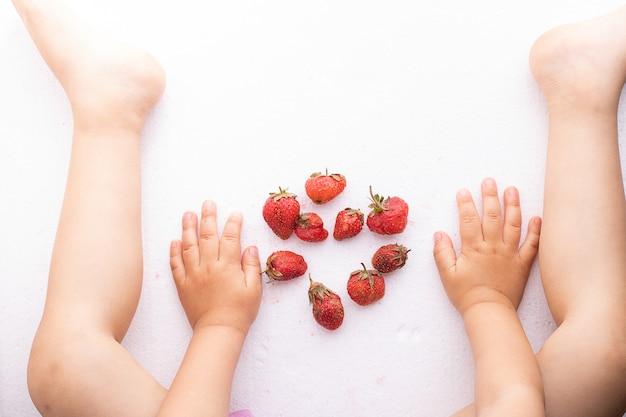 Kinderen handen en benen in de buurt van lelijke aardbeien, bovenaanzicht en kopie ruimte