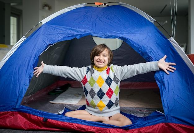 Kinderen hebben kampeertent in de woonkamer voor plezier en avontuur