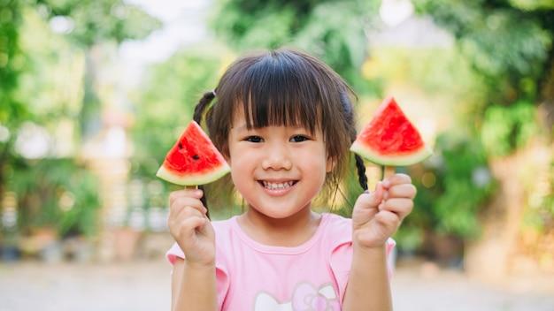 Kinderen hebben plezier en vieren de hete zomervakantie door watermeloen te eten