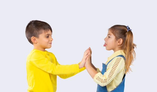 Kinderen hebben plezier. het meisje toont haar tong aan de jongen. witte achtergrond. het concept van emoties en de tijd die kinderen doorbrengen.