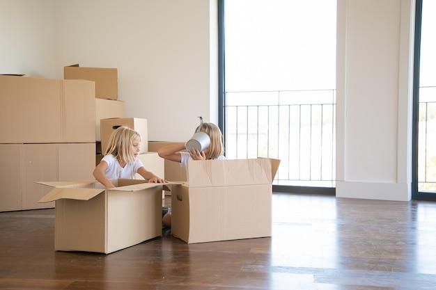 Kinderen hebben plezier tijdens het uitpakken van dingen in een nieuw appartement, zittend op de vloer en het nemen van voorwerpen uit open cartoon dozen