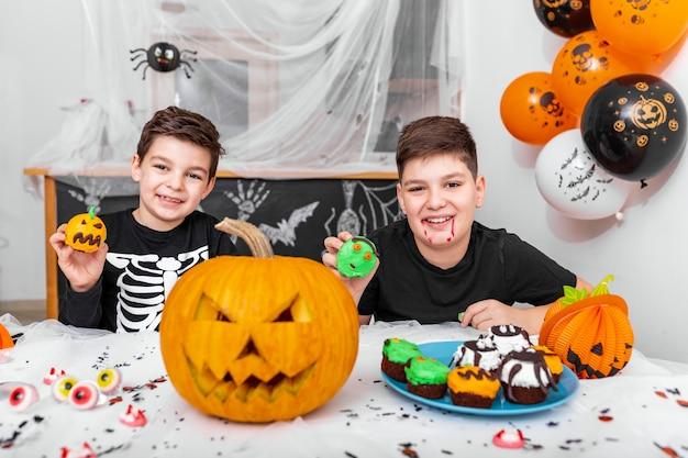 Kinderen hebben plezier voor halloween, omringd met enge decoratie die genieten van het eten van cupcakes. jack o 'lantern halloween-pompoen en cupcakes op tafel. fijne halloween!