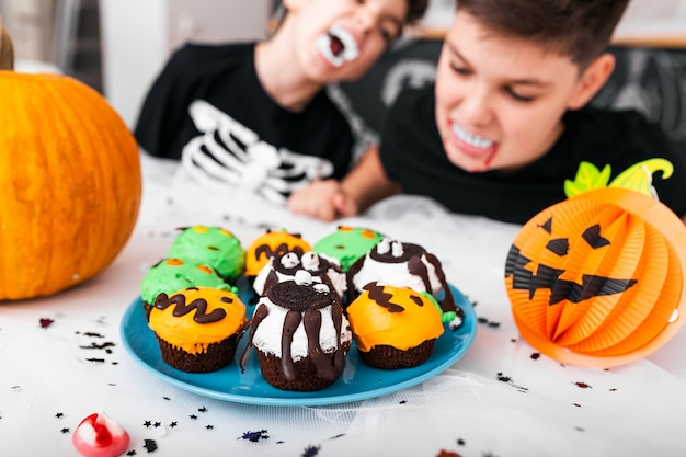 Kinderen hebben plezier voor halloween, omringd met enge decoratie. jack o 'lantern halloween-pompoen en cupcakes op tafel. fijne halloween!