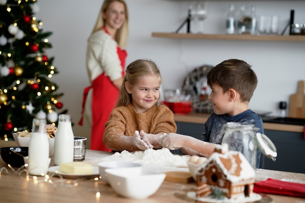 Kinderen hebben veel plezier tijdens het bakken van koekjes voor kerstmis