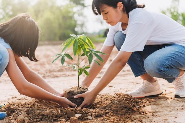 Kinderen helpen bij het planten van een boom in de tuin om de wereld te redden. eco milieu concept