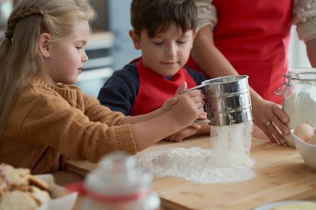 Kinderen helpen moeder met het bakken van kerstkoekjes