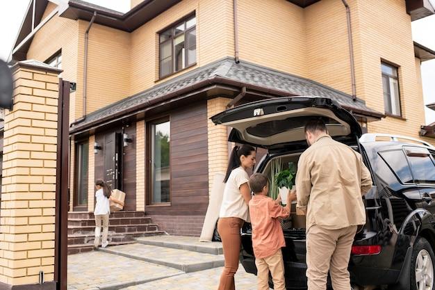 Kinderen helpen ouders met het uitladen van auto