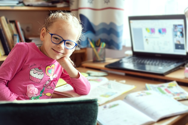 Kinderen homeschooling, gelukkig meisje, zittend aan tafel met laptop en schoolboeken