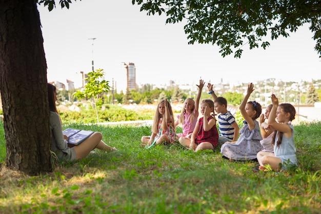 Kinderen houden een les met de leraar in het park op een groen gazon.