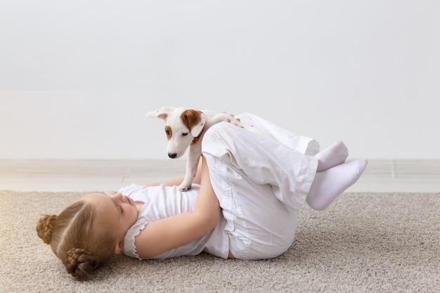 Kinderen, huisdieren en hondenconcept - klein schattig kindmeisje dat op de vloer ligt en speelt met grappige puppy jack russell terrier