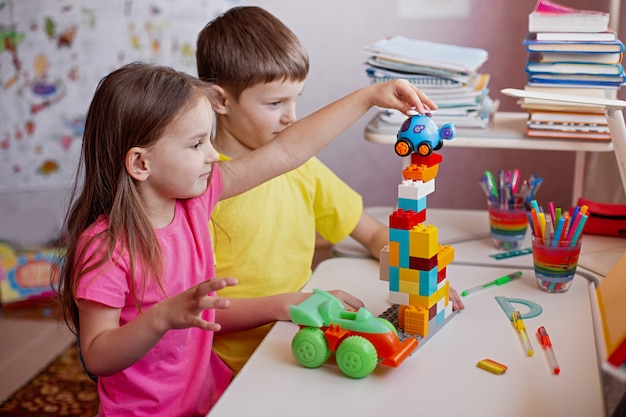 Kinderen huiswerk maken met schoolboeken en spelen met zijn favoriete speelgoed thuis