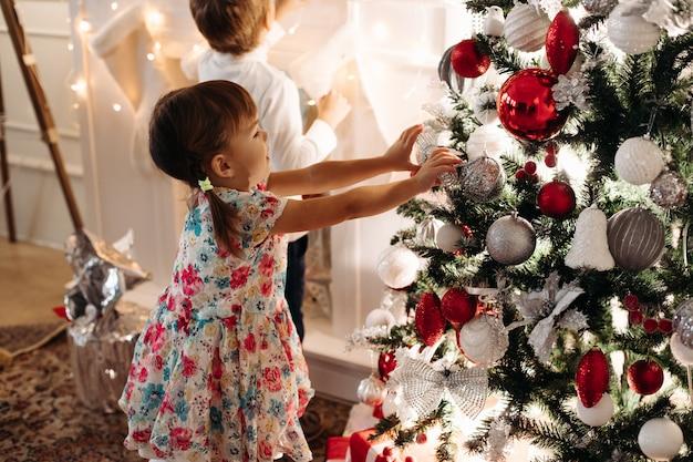 Kinderen in de buurt van een versierde kerstboom