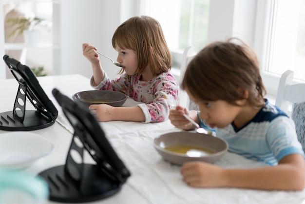 Kinderen in de eetkamer eten en kijken naar de tablet