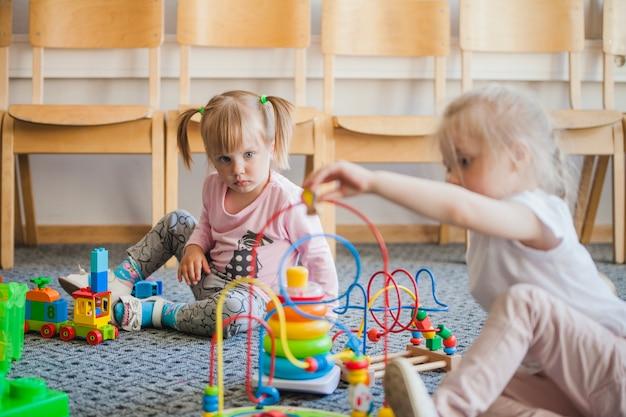 Kinderen in de kleuterschool met speelgoed