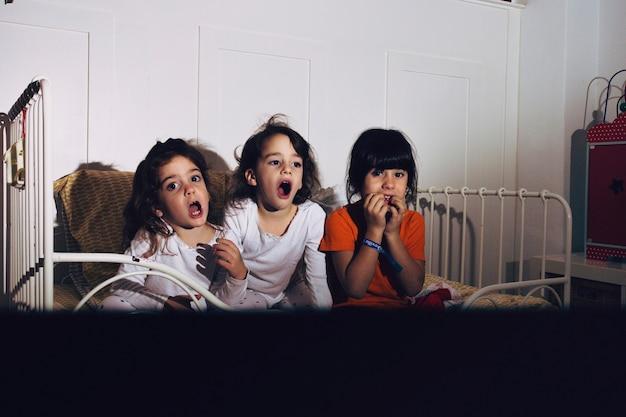 Kinderen in de slaapkamer kijken naar horrorfilm