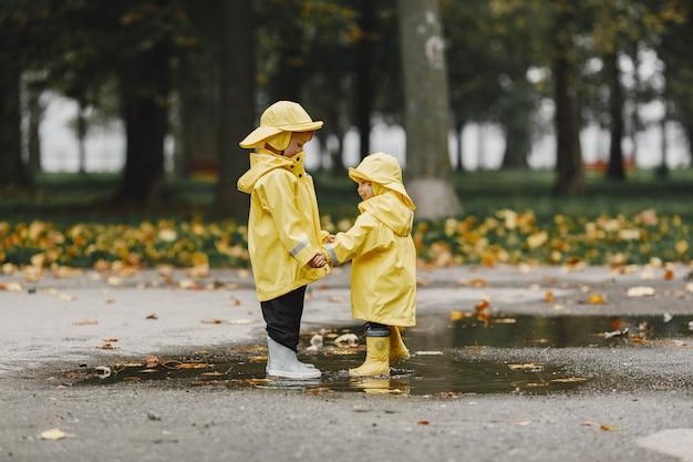 Kinderen in een herfstpark. kinderen in gele regenjassen. mensen hebben plezier buitenshuis.