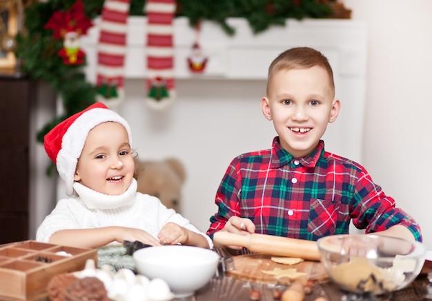 Kinderen in een kerstmuts kerstkoekjes thuis bakken.