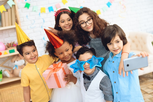 Kinderen in feestkleding en feestmutsen maken selfie.