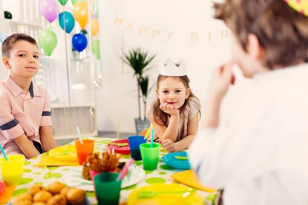 Kinderen in gekleurde caps zitten aan tafel
