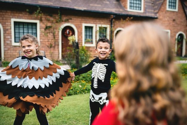 Kinderen in halloween-kostuums hand in hand in een park